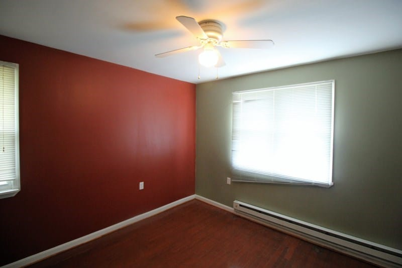 large room with two windows and ceiling fan