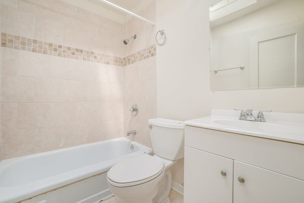 White Bathroom with Cream Bathtub Tiles at 345 Endsleigh Ave