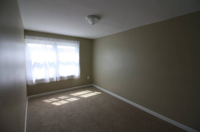 Carpeted Bedroom with Window and Curtain